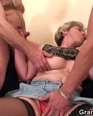 Hot grandma warms up before swallowing two cocks